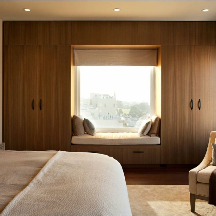 rincón de lectura acogedor en el dormitorio, habitación con mueble de madera, luces empotradas y moqueta