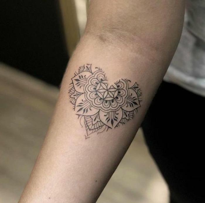 significado de tatuajes con corazones, tatuaje corazón en el antebrazo con motivos florales