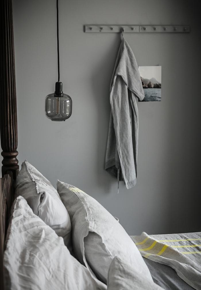 decoración dormitorio en grises, paredes en gris oscuro, cama de madera con marco, lámpara en estilo vintage