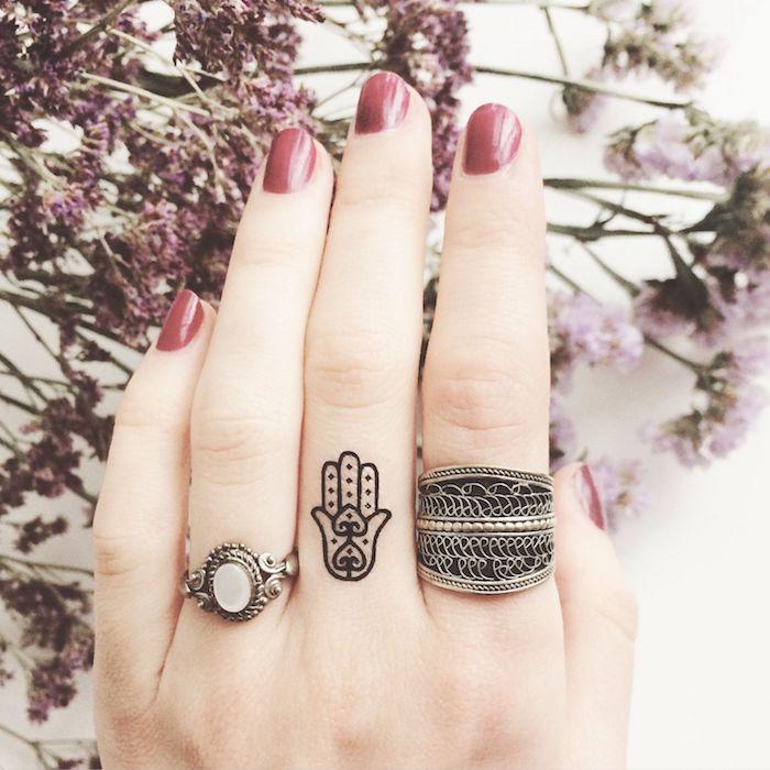 las mejores ideas de tatuajes pequeños para dedos, tattoo minimalista en el dedo corazón con significado