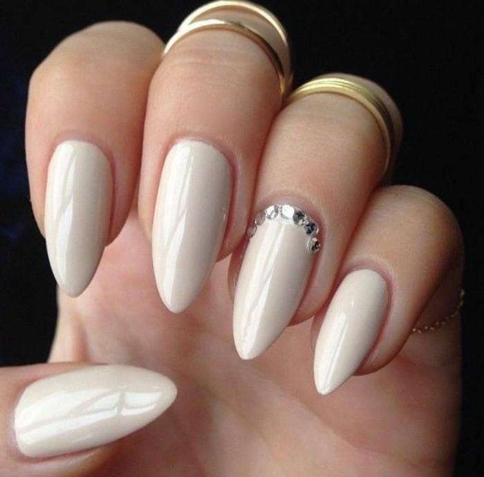 modelos de uñas con cristales y piedras, uñas largas afiladas pintadas en blanco con piedras relucientes