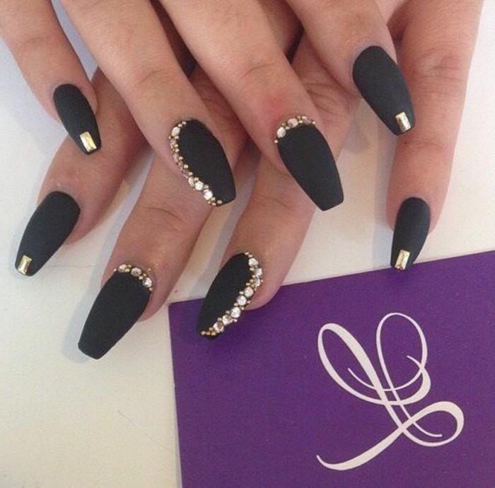 uñas largas pintadas en negro con acabado mate y piedras decorativas en dorado, uñas acrilicas decoradas