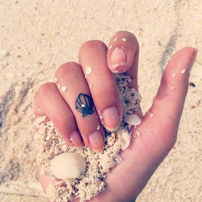 tatuajes dedos mujer pequeños con significado, pequeña concha tatuada en el dedo anular
