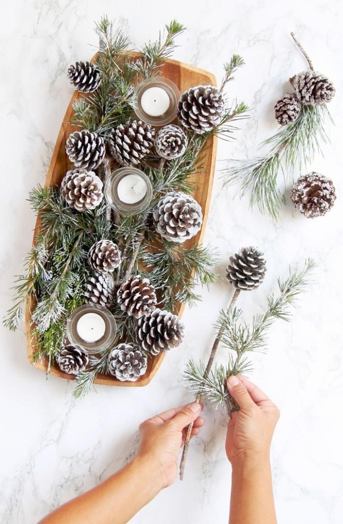 centro de mesa casero con ramos de pino y piñas pintadas en blanca, decoracion de mesa navideña