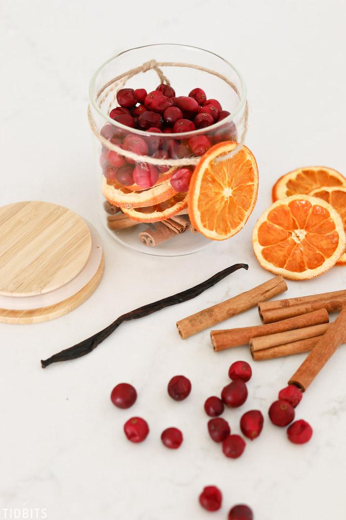 como hacer un popurrí para aromatizar la casa en navidad, frasco de vidrio lleno de frutas secas y palos de madera
