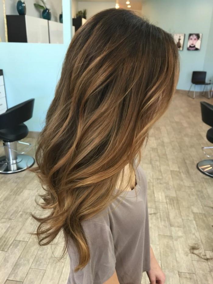 cabellera larga ondulada con balayage castaño en el pelo, mechas rubias en pelo oscuro