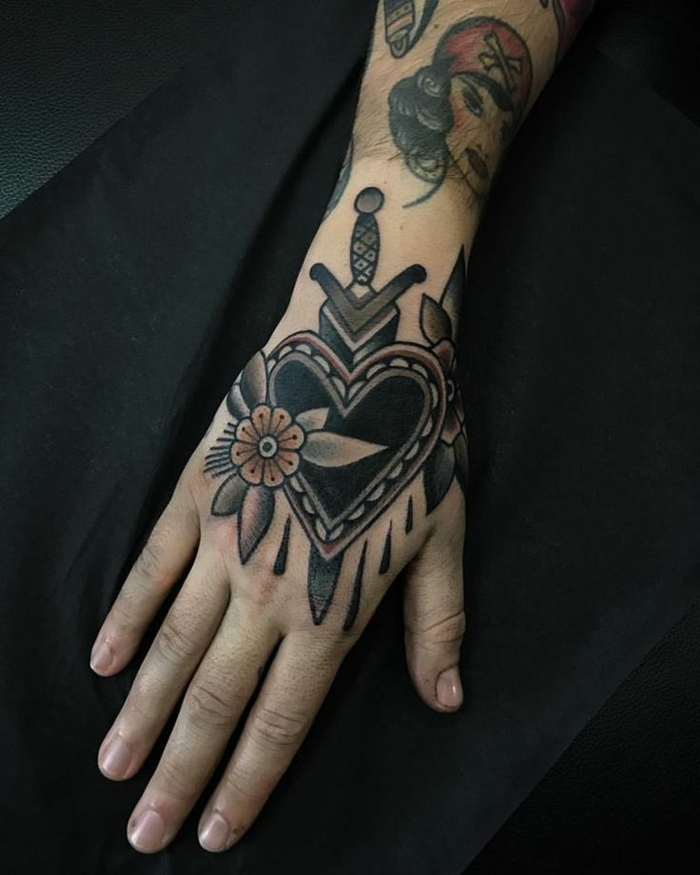 precioso tatuaje mano en estilo old school con corazón, espada y motivos florales, diseños de tattoos originales