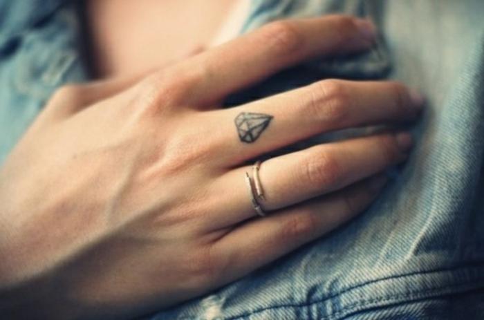 tatuajes pequeños mujer con fuerte significado, diseño de tatuaje con diamante en el dedo corazón