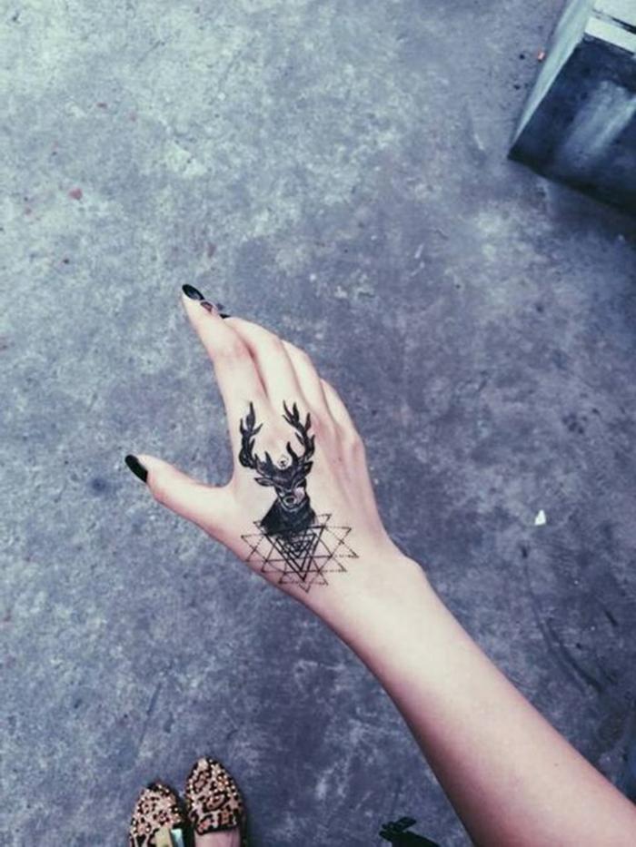 diseños de tattoos en la mano originales, tatuaje negro con reno en la mano, tatuajes simbólicos