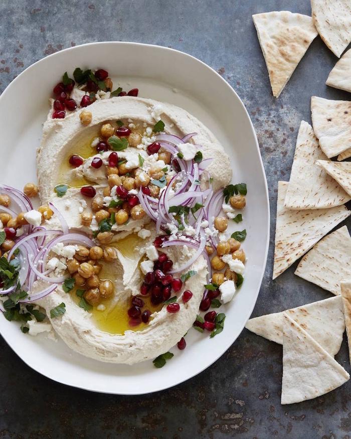 hummus casero con garbanzos, frutas de granada, perejil y cebolla roja, aperitivos veganos