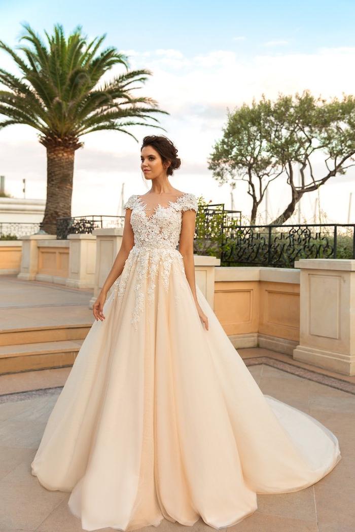 maravilloso vestido en color albaricoque, falda larga de tul en color crema y parte superior de bordado blanco, mujer con pelo recogido en moño