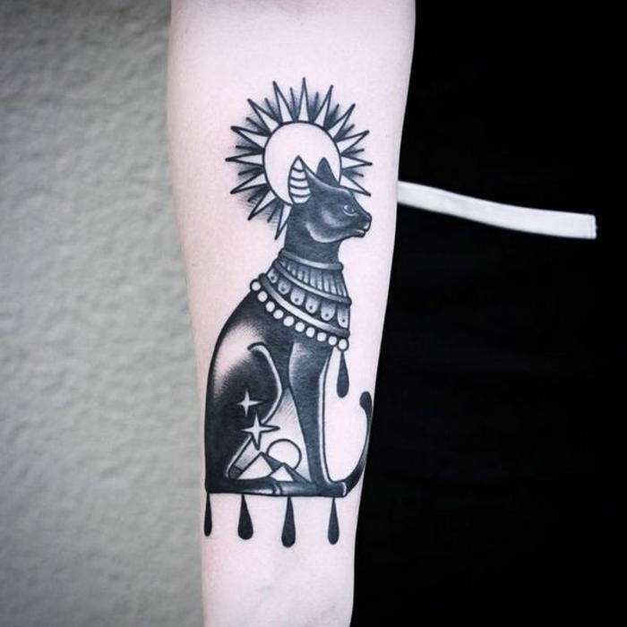 cuáles son los mejores diseños de tatuajes con simbolos egipcios, tatuajes de gatos simbolicos, gato negro y sol tatuados en el antebrazo