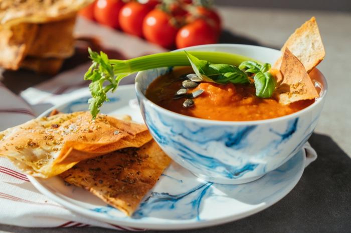 sopa de tomate adornada de semillas de calabaza, tallo de apio y orégano fresco, las mejores recetas para perder peso