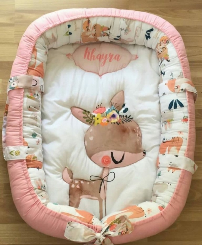 рegalos originales para recien nacidos y útiles, cama bebé bonita en color rosado con una pequeña cierva, originales ideas regalos bebé