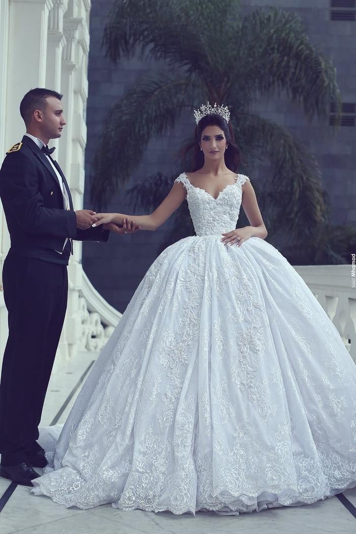 vestidos de novia clásicos de corte princesa, vestidos con larga y voluminosa falda, mujer con bonita corona ornamentada