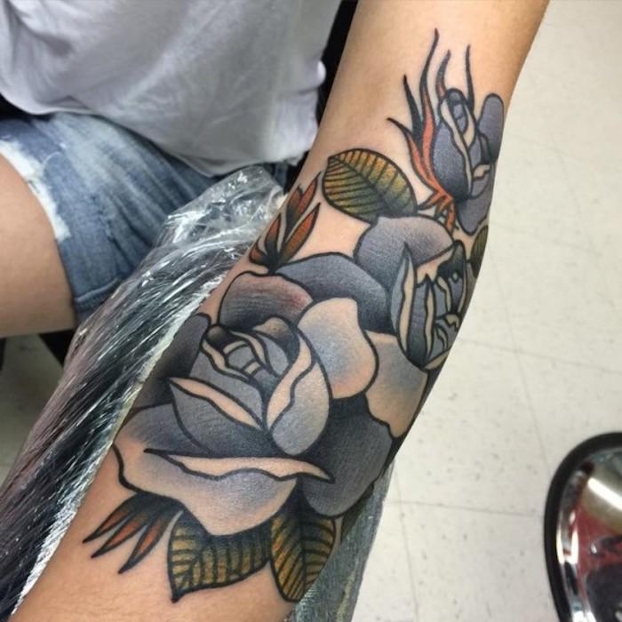 tatuaje en el antebrazo bonito con flores, precioso diseño con rosas con azul en elantebrazo, significado tattoos de flores