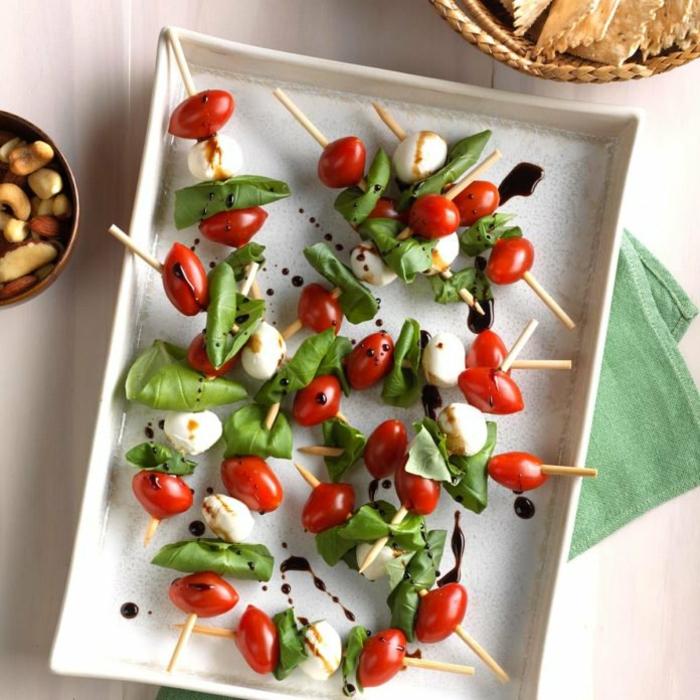 pinchos caprese para una cena de verano, pinchos con tomates, bolas de queso mozzarella y albahacas, aperitivos frios