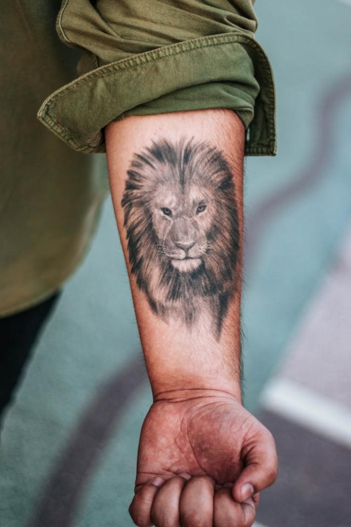 tatuaje león en estilo realista en el antebrazo, diseños de tatuajes originales con animales, tatuajes de animales significado