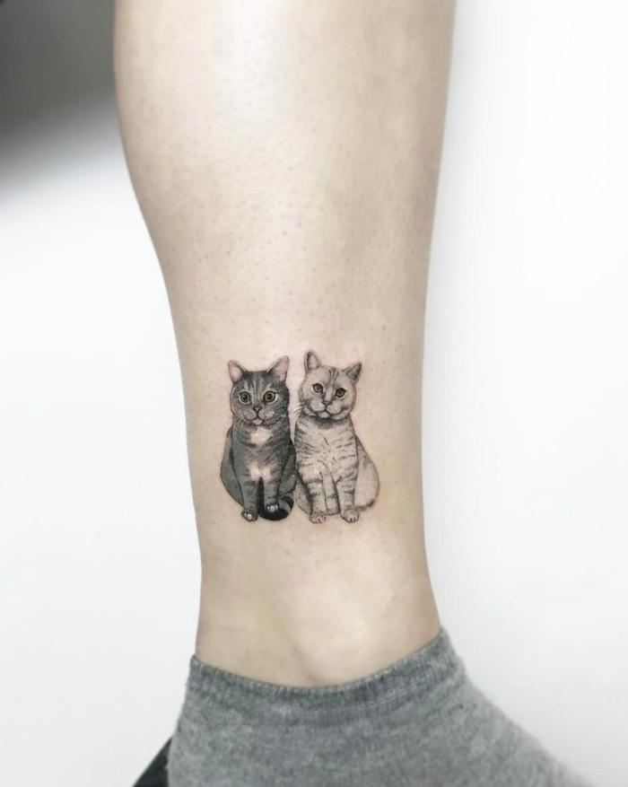 dos gatos tatuados en la pantorrilla, ideas de tatuajes originales de mascotas, diseños de tatuajes pequeños en la pierna