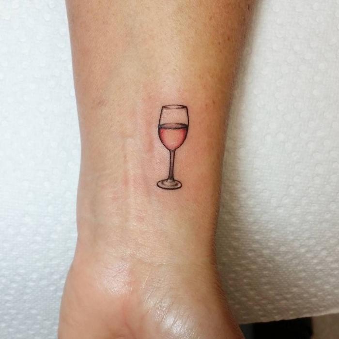 copa de vino tatuada en el antebrazo, tatuajes pequeños mujer, tatuajes simbolicos bonitos, copa de vino rosado