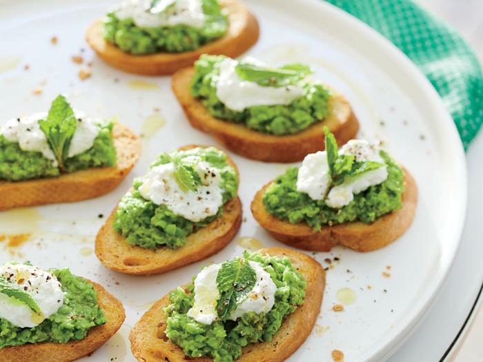 aperitivos sencillos y originales. tostadas con pesto casero y queso mozzarella adornadas de hojas de hierbabuena
