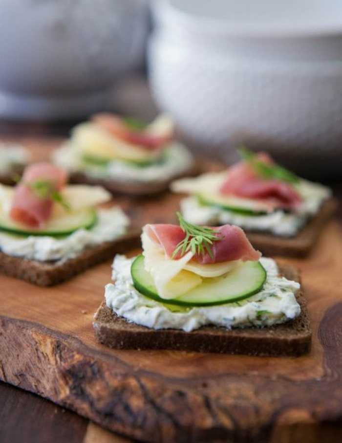 ejemplos de aperitivos sencillos y originales, tostadas integrales con crema de yogur y eneldo, pepinos, queso y jamón