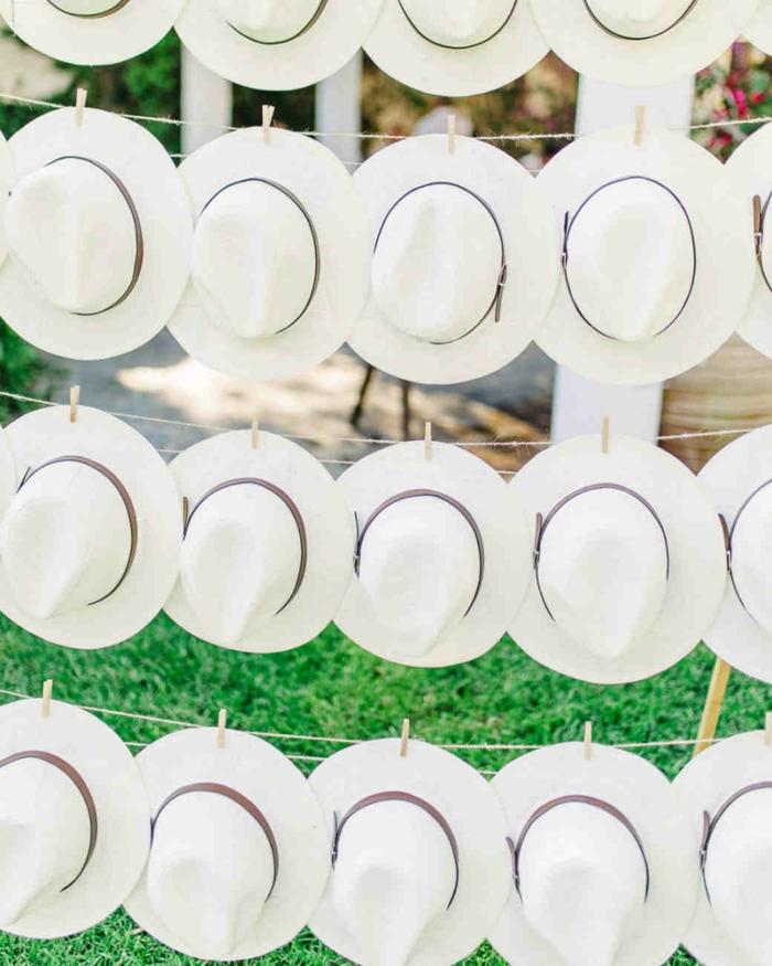 fotos de detalles de boda originales para regalar a los invitados, sombreros de verano en color blanco colgados en cordeles