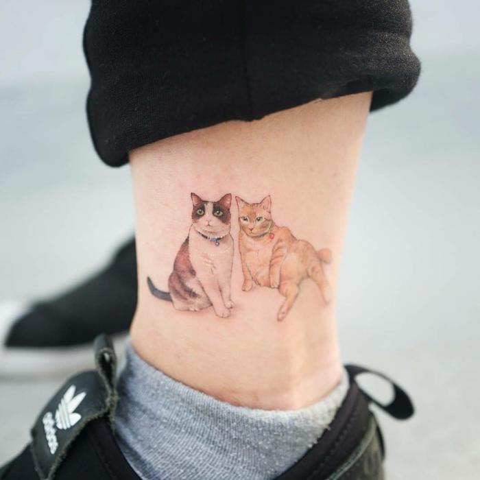 dos adorables gatos tatuados en la pantorrilla, tatuajes que signifiquen fuerza y superacion, tatuajes chicos en el tobillo