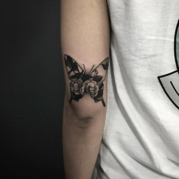 pequeña mariposa tatuada en el brazo, mariposa con flores con tinta negra, diseños de tatuajes que significan cambio y transformación