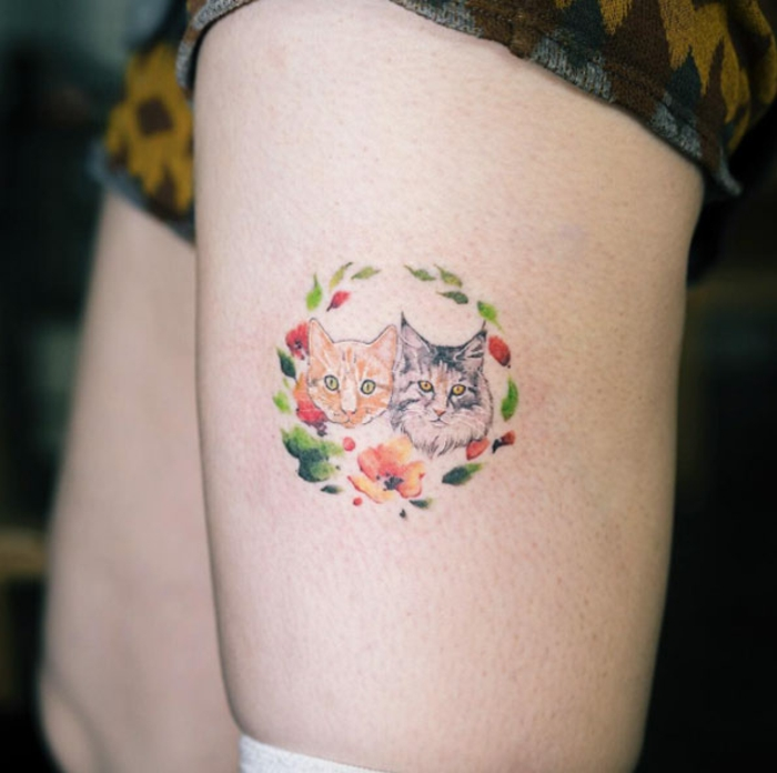 bonito diseño de tatuaje en la pierna con dos gatos y corona de flores, ideas de tatuajes familia de mascotas, tatuaje colorido
