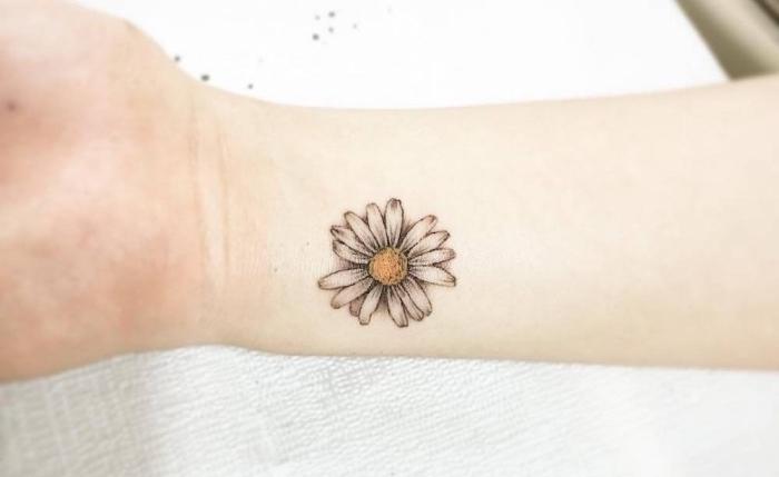 tatuajes chicos con flores, bonita margarita tatuada en el antebrazo, los mejores diseños de tatuajes pequeños para escoger