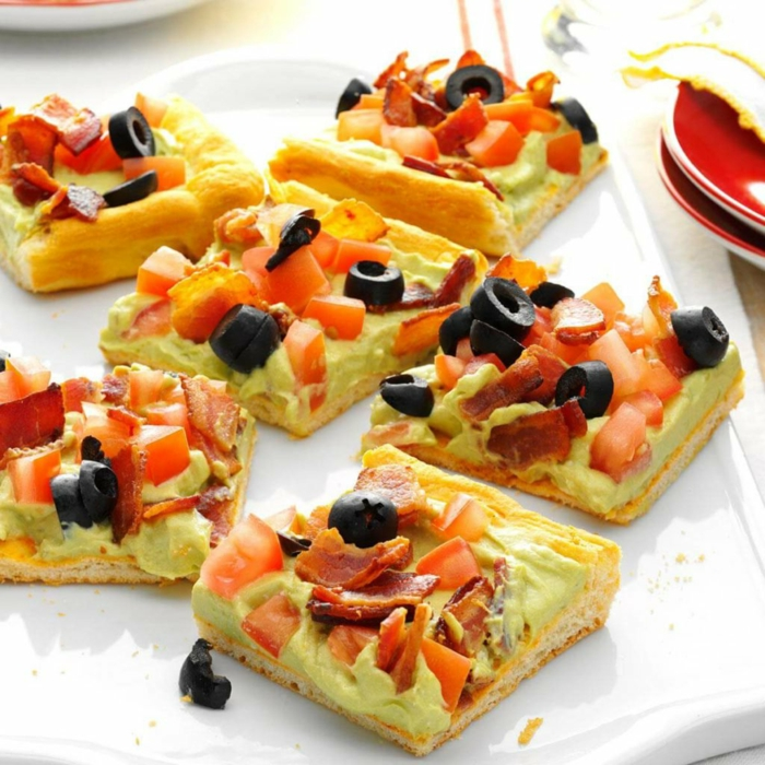 pizzas caseras con salsa de aguacate, tomates, tocino y aceitunas negras, canapes sencillos para hacer en casa paso a paso