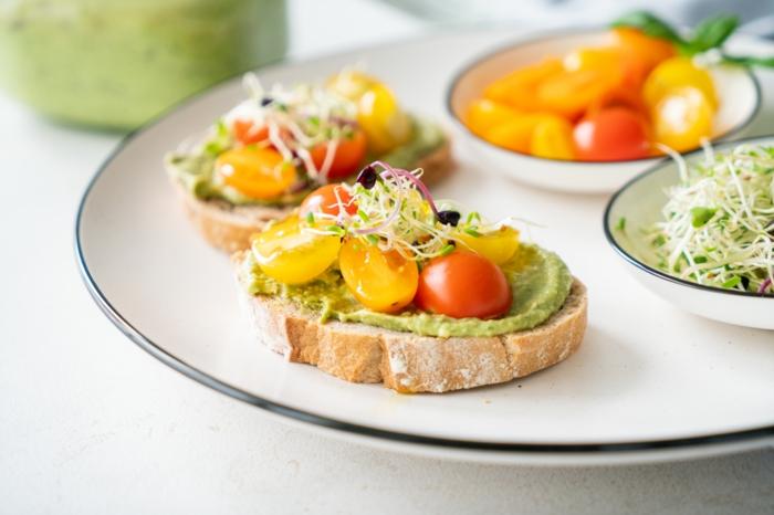tostadas con pesto casero, tomates uva y verduras, las mejores ideas de recetas con aguacate para una dieta equilibrada