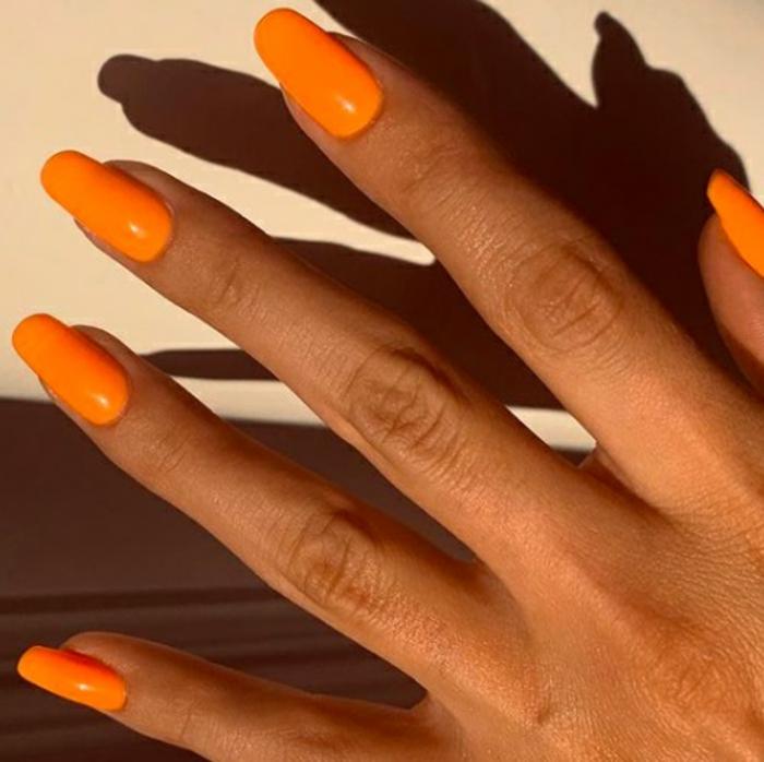 tendencias en las uñas primavera verano 2019, largas uñas pintadas en naranja neón, uñas de gel decoradas en imagines