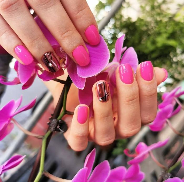 uñas cortas cuadradas pintadas en rosado con una uña en color cobrizo con decorado negro con perlas, preciosos diseños de uñas para el verano