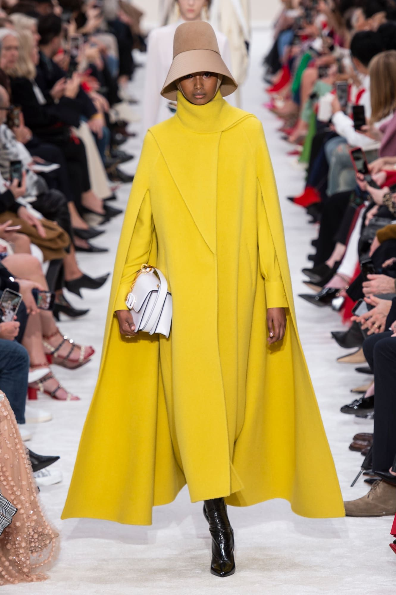 fotos de tendencias look invierno 2019, capa larga en color amarillo vibrante, capas maxy y abrigos 2019 2020, botas negras y bolso vintage color blanco