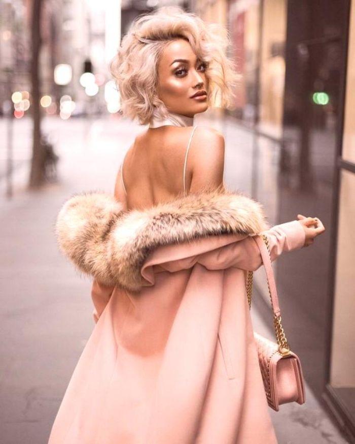 fotos con las tendencias otoño invierno 2019 mujer, abrigo en color rosado con un vestido elegante de espalda descubierta