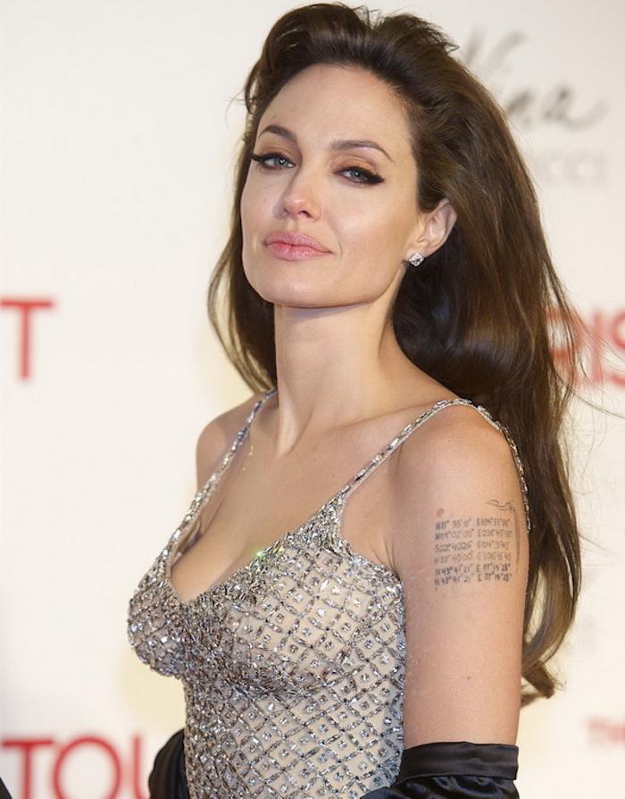 Angelina Jolie con un bonito vestido color plata y tatuaje chico en el hombro, originales ideas de tatuajes con letras