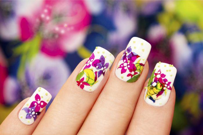 uñas de gel decoradas con preciosos dibujos de motivos florales, uñas largas pintadas en blanco con dibujos en colores vibrantes