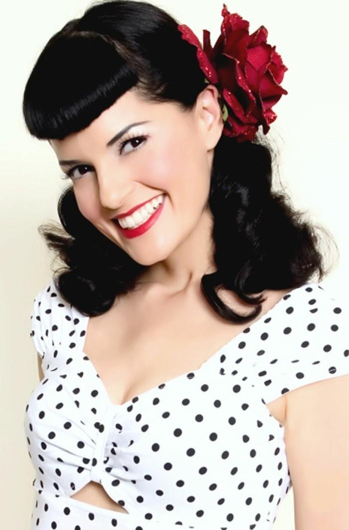 peinados rockabilly para media melena, maquillaje pin up con labios en color rojo, cabello negro con rizos y rosa en el pelo
