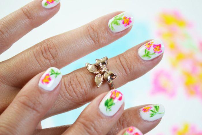 uñas de gel diseños en fotos, uñas cortas pintadas en blanco con dibujos de flores en colores vibrantes para el verano