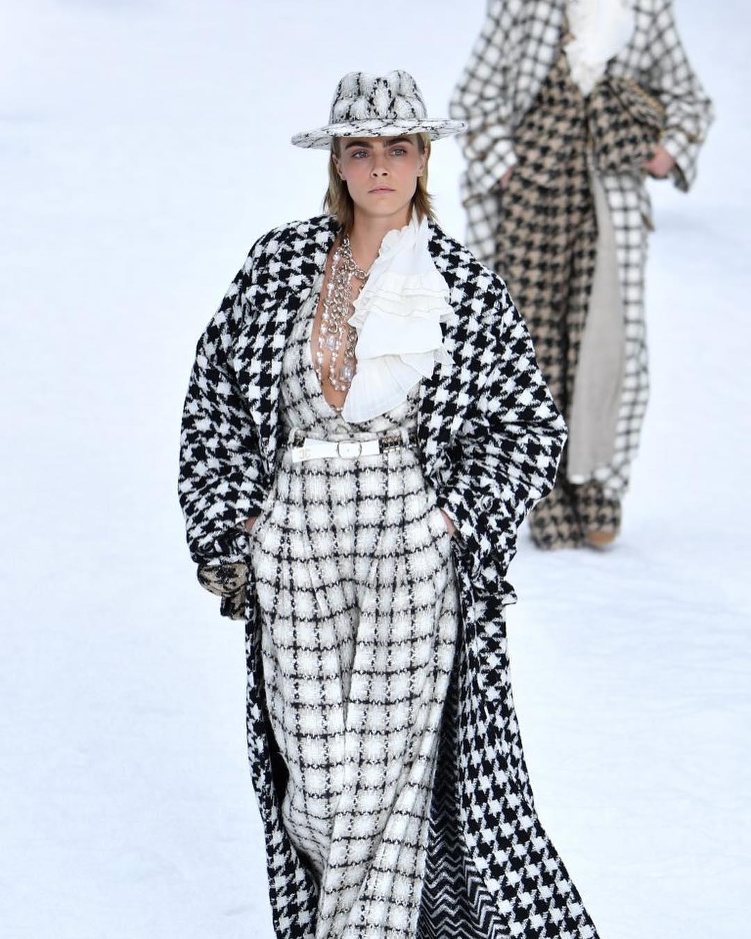 ideas de look invierno 2019, Cara Delevingne con un mono de lana blanco en cuadros negros, chaqueta larga en blanco y negro