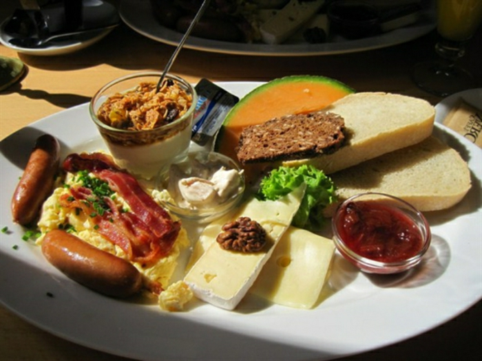 ingredientes para un brunch clásico para empezar el dí,a salchicas, queso brie, tostadas, frutas y huevos revueltos