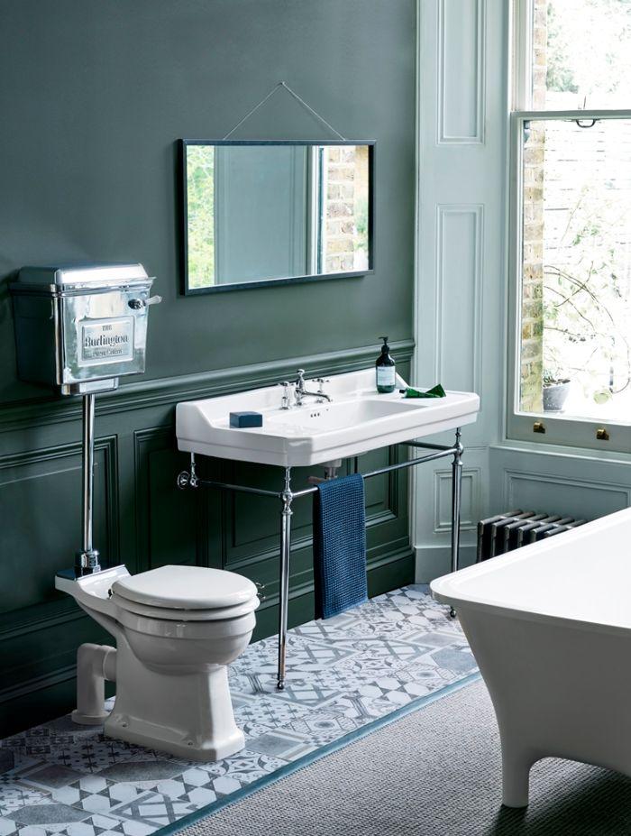 cuartos de baño decorados en colores oscuros, pequeño baño con paredes pintadas en color verde oscuro y suelo con azulejos ornamentados