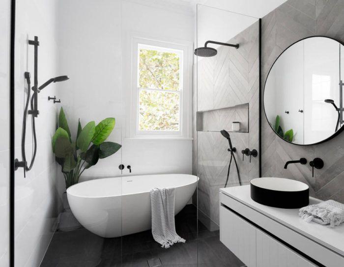 baño decorado en estilo bohemio con paredes blancas, suelo color negro, azulejos en las paredes y grande espejo oval