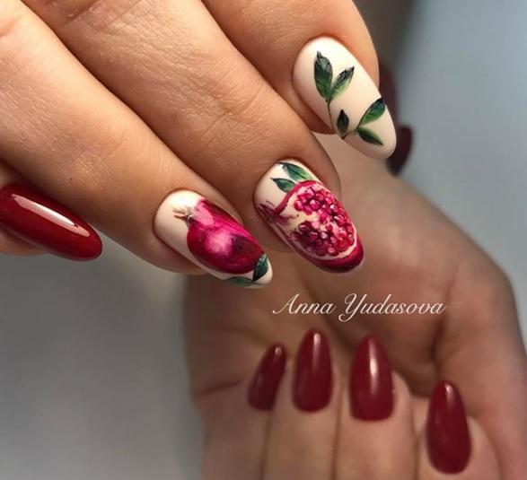 ejemplos de dibujos para uñas de frutas, preciosas muestras de nail art, uñas largas almendradas en rojo y beige con dibujos de granada