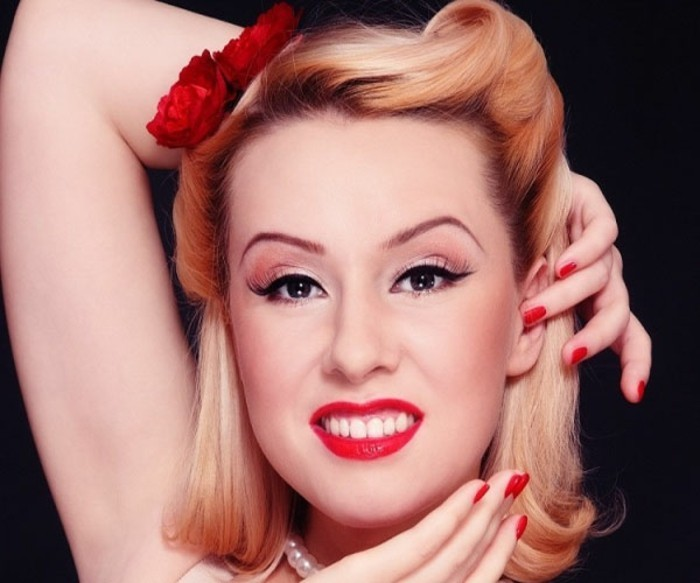 apariencia retro, cabello corto en un bonito peinado estilo pin up con rosas en el pelo, maquillaje retro clásico con labios rojos