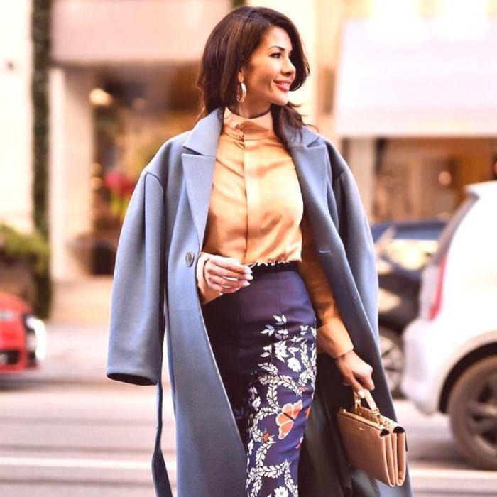 precioso outfit con falda larga con motivos florales, camisa en color naranja suave, abrigo largo en azul pastel y bolso en beige