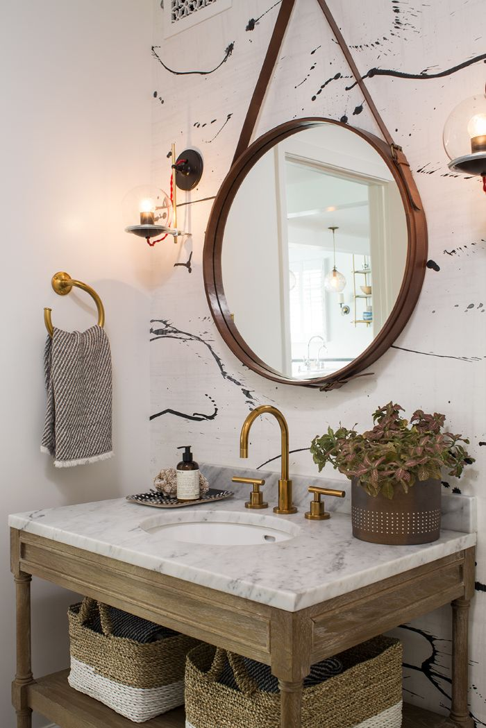 cuarto de baño en estilo bohemio, pequeño lavabo con detalles de madera y mimbre, espejo de forma oval colgado en la pared