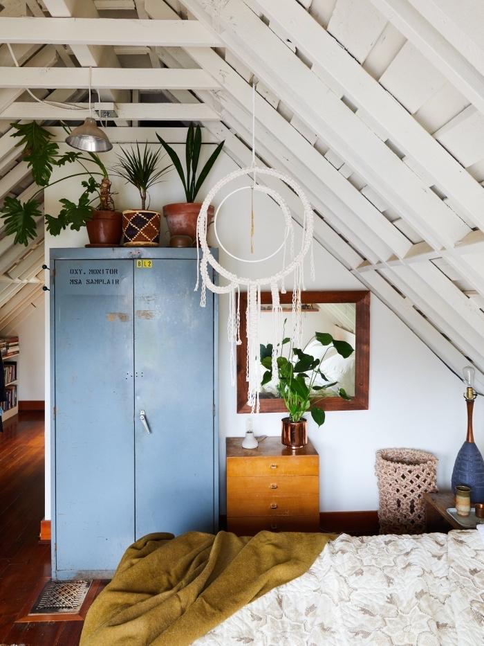 salón abuhardillado pintado en blanco con muebles en colores, plantas verdes y muebles y objetos de madera en estilo vintage